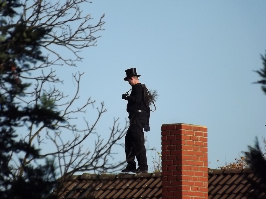 Chimney Sweep with tophat standing on roof next to brick chimney